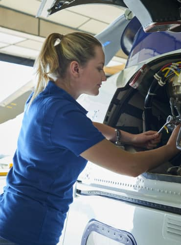 a female engineer works on an airplane