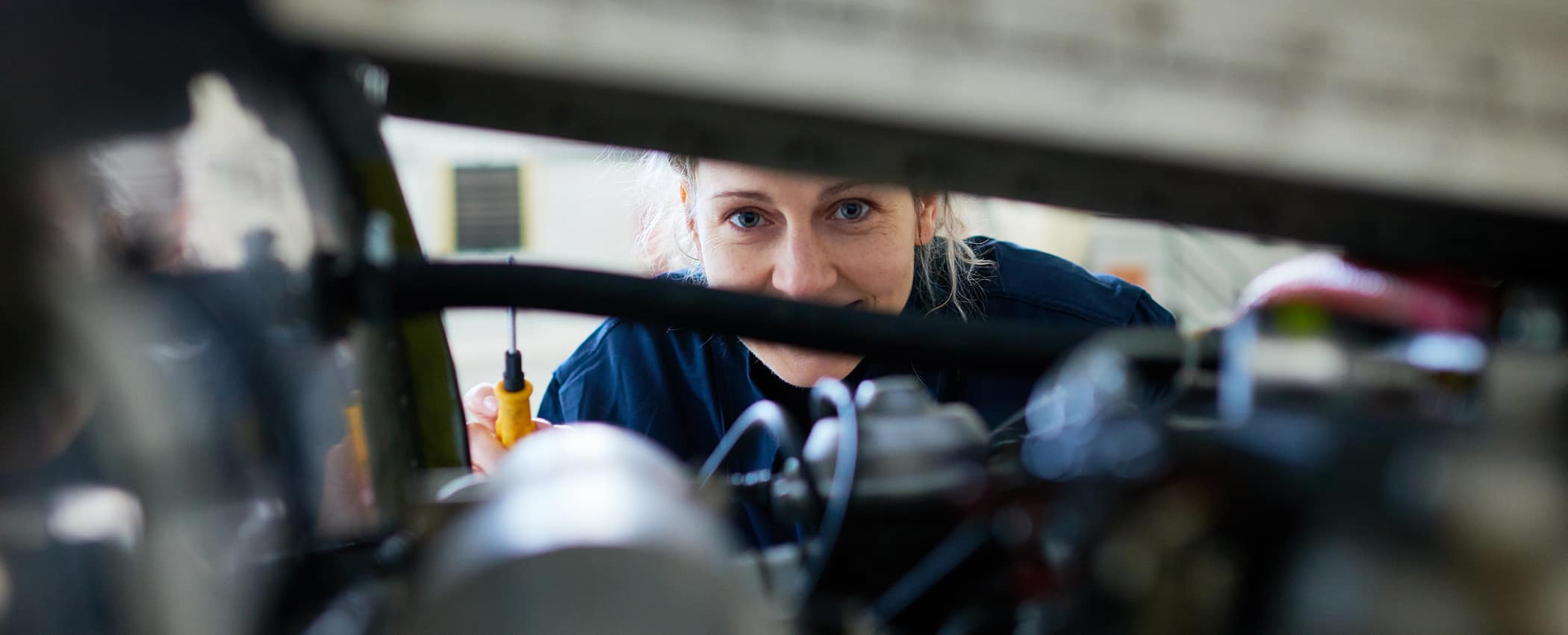 a female engineer looks over a plane engine