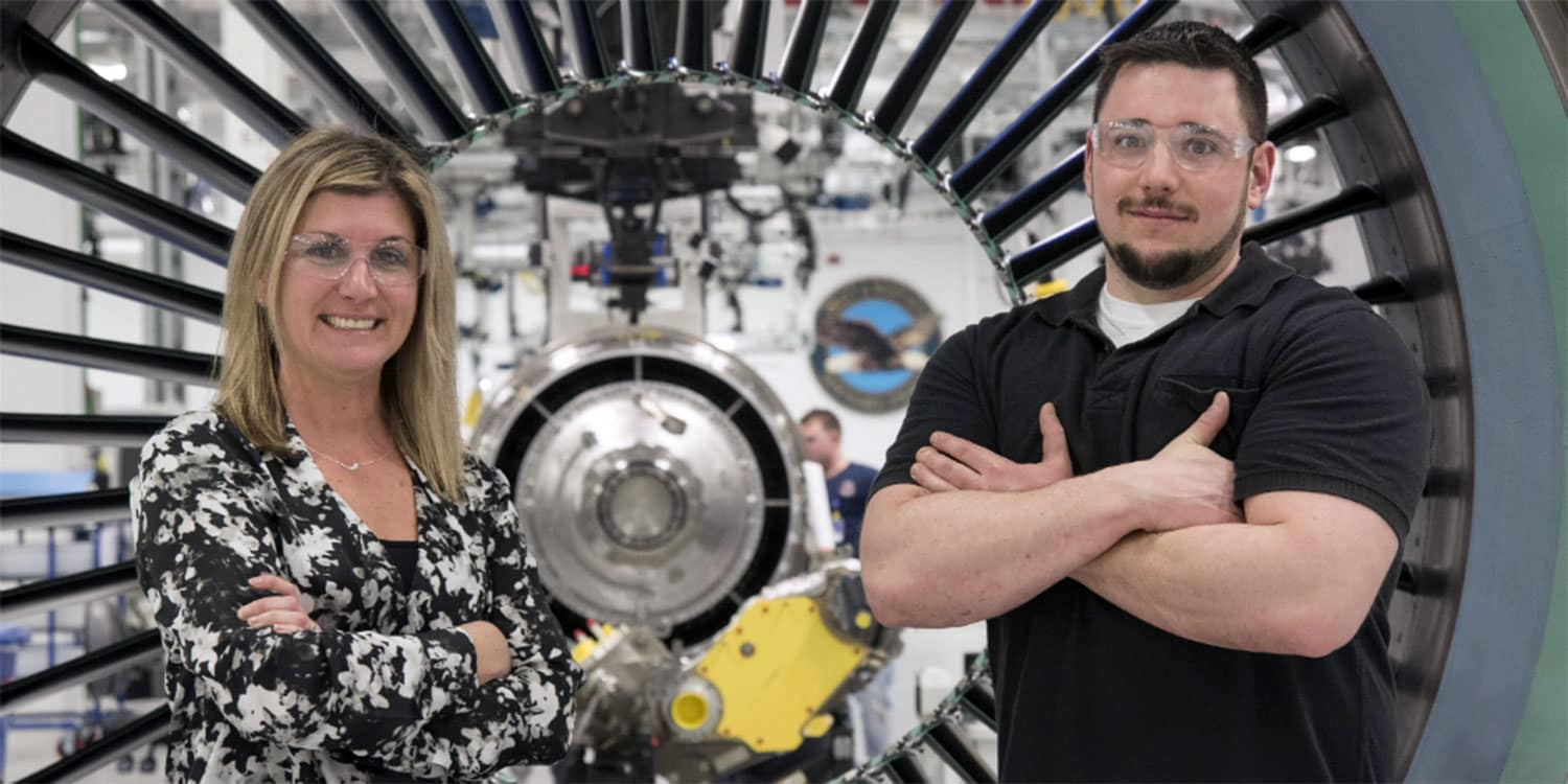 a woman and a man in front of an airplane engine