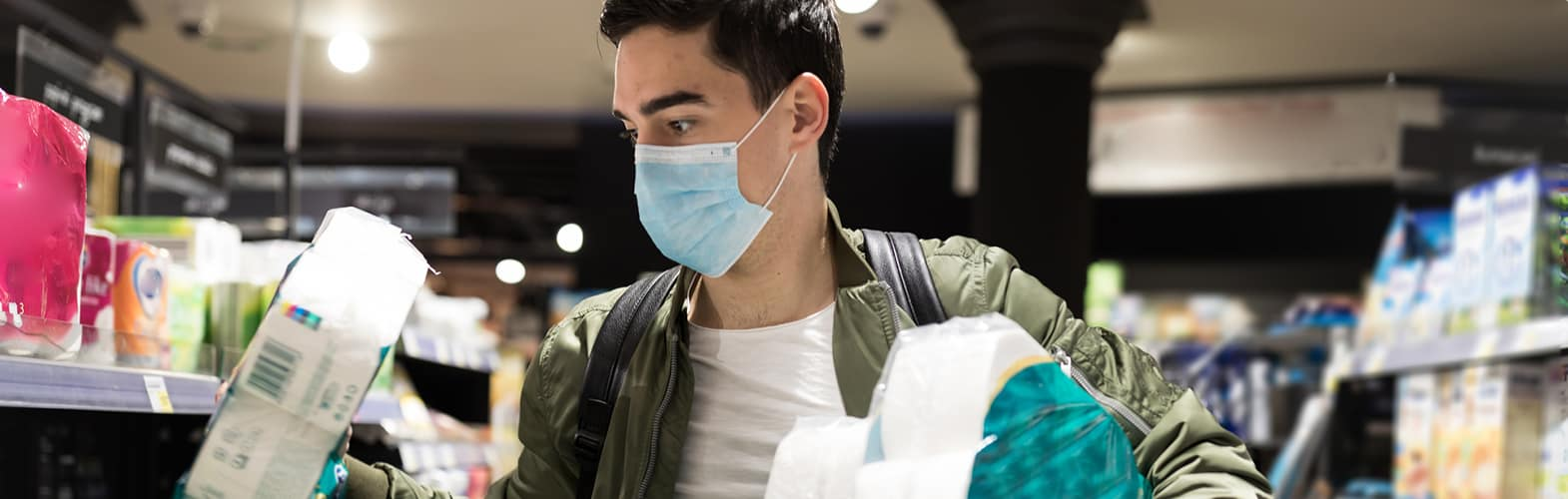Young Man shopping in a supermarket for toilet paper wearing a medical mask.