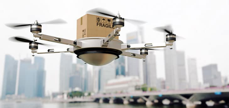 This is a photo of a drone carrying a package in a big city.